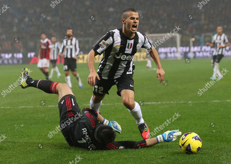 Juventus forward Sebastian Giovinco, challenge for the ball with AC Milan goalkeeper Marco Amelia during a Serie A soccer match between AC Milan and Juventus, at the San Siro stadium in Milan, Italy