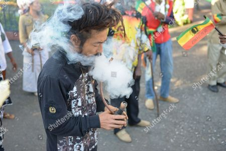 "A Rastafarian named Bongho Jatusy smokes a pipe of marijuana outside a museum dedicated to the memory of late reggae icon Bob Marley in Kingston, Jamaica. While marijuana is still illegal in Jamaica, where it is known popularly as ""ganja,"" increasingly vocal advocates say that Jamaica could give its struggling economy a boost by taking advantage of the fact the island is nearly as famous for its marijuana as it is for beaches, reggae music and world-beating sprinters"