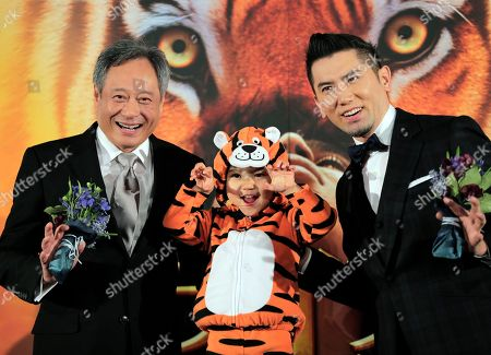 """Ang Lee, Masahiro Motoki, Shizuku Director Ang Lee, of Taiwan, left, poses for photographers with Japanese guests, actor Masahiro Motoki, righ, and child actress Shizuku during the Japan premiere of his 3D film """"Life of Pi,"""" in Tokyo, . The film will be released in Japan on Jan. 25"""