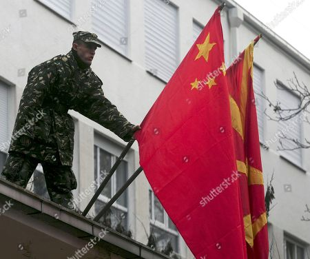 Stock Image of Macedonian Army soldier fixes the Chinese flag next to the Macedonian, prior the arrival of the Minister of National Defense of People's Republic of China and State Chancellor, General Liang Guanglie, not pictured, at the Macedonian Ministry of Defense in the capital Skopje, on . This is the first visit of a Chinese Defense Minister to Macedonia