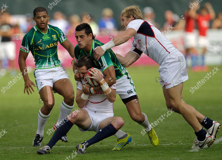 U.S. player Zach Test, bottom, is tackled by South Africa's Carlin Isles during the final day of Emirates Airline Dubai Rugby Sevens in Dubai, United Arab Emirates