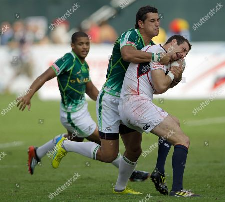 U.S. player Zach Test, right, is tackled by South Africa's Carlin Isles during the final day of Emirates Airline Dubai Rugby Sevens in Dubai, United Arab Emirates