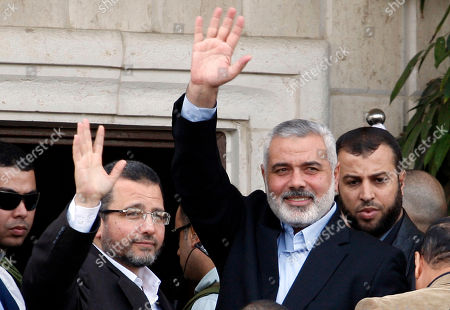 Hesham Kandil, Ismail Haniyeh Gaza's Hamas Prime Minister Ismail Haniyeh, right, and Egyptian Prime Minister Hesham Kandil, left, waves to the crowd as they meet in Gaza City. An Egyptian court ruled on Tuesday, March 4, 2014 to ban activities of the Palestinian militant group Hamas in Egypt in a move likely to fuel tension between Cairo's military-backed government and the Islamic group that rules the neighboring Gaza Strip. Egypt's interim leaders maintain that Hamas is playing a key role in the insurgency by militants in the northern region of the Sinai Peninsula, which borders Hamas-ruled Gaza and Israel