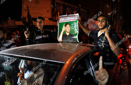Palestinian gunmen hold a poster of late Ahmed Jabari, head of the Hamas military wing in Gaza City, while they celebrate the cease-fire agreement between Israel and Hamas in Gaza City, . Israel and the Hamas militant group agreed to a cease-fire Wednesday to end eight days of the fiercest fighting in nearly four years, promising to halt attacks on each other and ease an Israeli blockade constricting the Gaza Strip