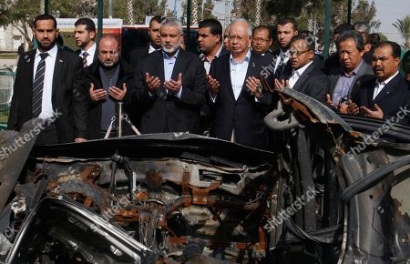 Gaza's Hamas prime minister Ismail Haniyeh, third left, and Malaysian Prime Minister Najib Razak, forth right, pray next to a wreckage of a car in which Hamas military leader Ahmed Jabari was killed in an Israeli attack on Nov. 14, 2012, upon Razak's arrival in Rafah, southern Gaza Strip, . During his first-ever visit to the territory Tuesday, Najib Razak is meeting with Hamas politicians, touring sites bombed by Israeli forces and visiting a school funded by his majority-Muslim nation in Southeast Asia