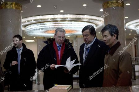 """Eric Schmidt, Bill Richardson, Jared Cohen Executive Chairman of Google, Eric Schmidt, second from left, and former Governor of New Mexico Bill Richardson, second from right, look through an information technology text book at the Grand People's Study House in Pyongyang, North Korea on . At left is director of Google Ideas think tank, Jared Cohen. The textbook is titled """"Aries Net+ Certified Technician First Edition Version 3.0"""
