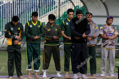 Pakistan's former test cricketer Inzamam-ul-Haq, front, leads a prayer at Qaddafi stadium during a practice session for the short cricket tour of India this month, in Lahore, Pakistan