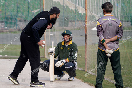 Pakistan's former skipper of cricket team and batting consultant Inzamam-ul-Haq, left, gives tips to Shahid Afridi, center, during a training camp at Gaddafi Staduim in Lahore, Pakistan on . Haq advised his batsmen to play positively when the limited-overs series against archrival India starts later this month and predicts the team that handles the pressure better will emerge the winner