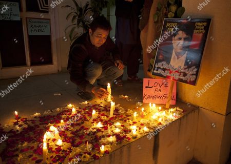"""Friends and colleagues of Pakistani officer Kamran Faisal light candles outside his residence in Islamabad, Pakistan, on . Officer Faisal was investigating a corruption case against the prime minister and was found dead in what police are calling a likely act of suicide. Faisal's death came days after the Supreme Court ordered the arrest of Prime Minister Raja Pervaiz Ashraf and 15 others in connection with an old corruption case that the officer was investigating. Writing on Faisal's poster reads """"who is my killer"""