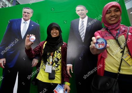 """Fatimatuzzahra Abdulmajid, Natasha Omar Muslim students, Natasha Omar, right, and Fatimatuzzahra Abdulmajid, display their respective pins as they pose for souvenir shots before the cutout figures of Republican challenger Mitt Romney, left, and incumbent US President Barack Obama during a U.S. Elections Watch at a shopping mall at suburban Quezon city, northeast of Manila, Philippines, . Filipinos participated in a mock US elections between Obama and Romney which was organized by the U.S. Embassy in Manila. Natasha """"voted"""" for Obama while Fatima """"voted"""" for Romney"""