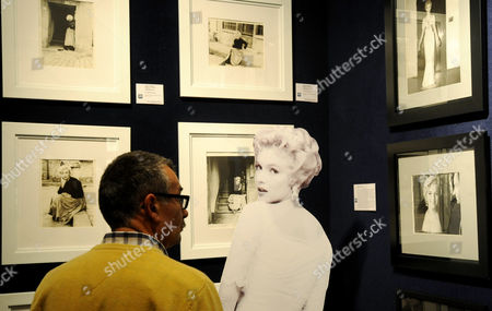 A potential bidder looks at Marylin Monroe photos prior to an auction of pictures by the late celebrity photographer Milton H. Greene, in Warsaw, Poland, . Some 238 pictures by Greene including portraits of Marylin Monroe, along with Cary Grant, Frank Sinatra, Audrey Hepburn, Liza Minnelli, Marlene Dietrich, Paul Newman, Alfred Hitchcock and Marlon Brando, were auctioned off in Warsaw with highest bids reaching 60.000 Polish zlotys (18.700 US dollars, or 14.400 euros) . Proceeds from the auction will go to the Polish state which owns a collection of around 4,000 pictures by Greene that ended up in Poland's possession as the result of a complex embezzlement scandal that shook the country in the early 1990s