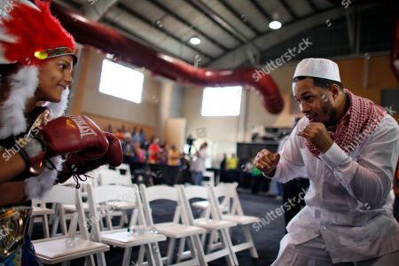 """Stock Image of Hector Camacho Jr., Alexander Birriel Hector Camacho Jr. right, playfully spars with Alexander Birriel, 10, during a memorial for his father, the former boxing champion Hector """"Macho"""" Camacho in San Juan, Puerto Rico, . Birriel honored Camacho by wearing an Indian headdress, symbolizing one of the many outfits the flamboyant Camacho was known for wearing in ring. Hundreds of people took pictures and filed past Camacho's open casket displayed inside a gymnasium. The boxer wore white, along with a large gold crucifix and a necklace spelling out his nickname, """"Macho,"""" in capital letters"""