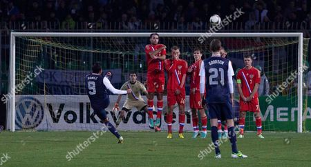 Herculez Gomez, of the United States, left, makes a free kick against Russia's goalkeeper Vladimir Gabulov, center right, during the friendly soccer match between Russia and United States, in Krasnodar, Russia, on . Game ended with 2-2 draw