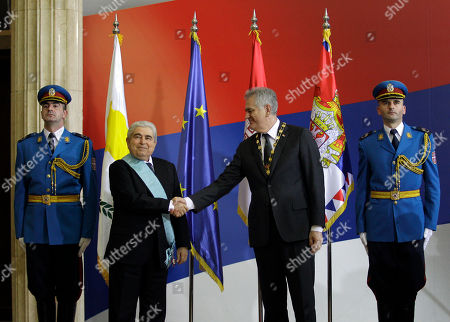 """Serbian President Tomislav Nikolic, right, shakes hands with his Cypriot counterpart President Dimitris Christofias, in Belgrade, Serbia, . Christofias is on a one day visit to Serbia, and is seen wearing the """"Order of Serbia"""" medal after it was presented by Nikolic"""