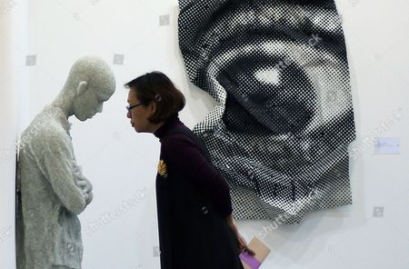 """A woman examines a sculpture entitled """"Figure with Arms Crossed"""" by American artist Daniel Arsham at the Marina Bay Sands convention center where international artists and art galleries convene at the Art Stage Singapore 2013 exhibition and trade show, in Singapore"""