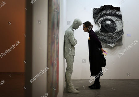 """A woman examines a sculpture titled """"Figure with Arms Crossed"""" by American artist Daniel Arsham on in Singapore at the Marina Bay Sands convention center where international artists and art galleries convene at the Art Stage Singapore 2013 exhibition and trade show"""