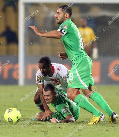 Algeria's Djamel Mesbah, bottom, defends against Tunisia's Saber Khalifa, back, as teammate Medhi Lacen, right, looks on during their African Cup of Nations Group D soccer match at Royal Bafokeng Stadium in Rustenburg, South Africa