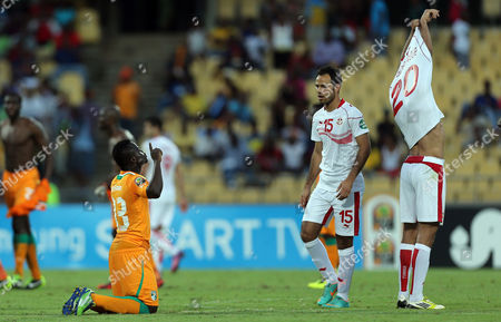 Ivory Coast's Ya Konan, left, celebrates the end of the match as Tunisia's Khelil Chammam, second right, looks, after their African Cup of Nations Group D soccer match at the Royal Bafokeng Stadium in Rustenburg, South Africa