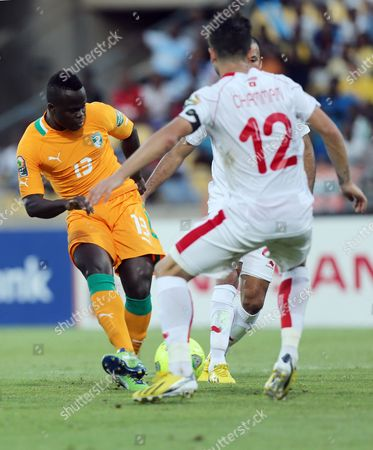 Ivory Coast's Ya Konan, left, scores a goal as Tunisia's Khelil Chammam, right, fails to defend during their African Cup of Nations Group D soccer match at the Royal Bafokeng Stadium in Rustenburg, South Africa