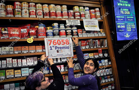 "Laura Leon, 30, right, and Pili Medina, 48, who sold one of the winning lottery tickets with the numbers, 76058, of the top prize of Spain's Christmas lottery known as ""El Gordo"" or ""The Fat One"" number, celebrates this, in her lottery shop, in the small town of Tudela, northern Spain, around 300 kilometers from Madrid. After a brutal year of economic hardship that deepened with unemployment hitting 25 percent, Spaniards across the country Saturday were hoping for relief from payouts by the nation's famed Christmas lottery, the world's richest, with euro 2.5 billion ($3.3 billion) in tax-free awards"