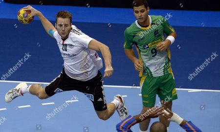 Kevin Schmidt, Lucas Candido Germany's Kevin Schmidt, left, leaps in the air to score past Brazil's Lucas Candido during their preliminary round Group A Men's World Handball championship match in Granollers, Spain