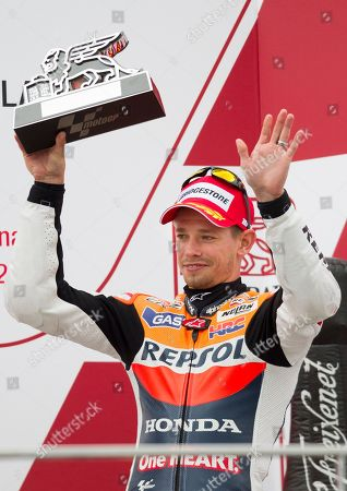 Dani Pedrosa MotoGP rider Casey Stoner from Australia gestures as he holds hise trophy at the end of the Motorcycle Grand Prix at the Ricardo Tormo circuit in Cheste near Valencia, Spain, . Dani Pedrosa won the season-ending Valencia Grand Prix after starting from the pit lane and taking advantage of world champion Jorge Lorenzo's crash on Sunday. Katsuyuki Nakasuga was second on his Yamaha, more than 37 seconds behind, while retiring two-time world champion Casey Stoner earned his 69th career MotoGP podium with a third-place finish in his final race
