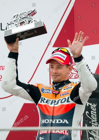 MotoGP rider Casey Stoner from Australia gestures as he holds hise trophy at the end of the Motorcycle Grand Prix at the Ricardo Tormo circuit in Cheste near Valencia, Spain, . Dani Pedrosa won the season-ending Valencia Grand Prix after starting from the pit lane and taking advantage of world champion Jorge Lorenzo's crash on Sunday. Katsuyuki Nakasuga was second on his Yamaha, more than 37 seconds behind, while retiring two-time world champion Casey Stoner earned his 69th career MotoGP podium with a third-place finish in his final race