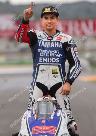 Jorge Lorenzo 2012 FIM MotoGP World Champion, Jorge Lorenzo, from Spain gives the thumb up as he poses for photographers at the end of the Motorcycle Grand Prix at the Ricardo Tormo circuit in Cheste near Valencia, Spain, . Dani Pedrosa won the season-ending Valencia Grand Prix after starting from the pit lane and taking advantage of world champion Jorge Lorenzo's crash on Sunday. Katsuyuki Nakasuga was second on his Yamaha, more than 37 seconds behind, while retiring two-time world champion Casey Stoner earned his 69th career MotoGP podium with a third-place finish in his final race