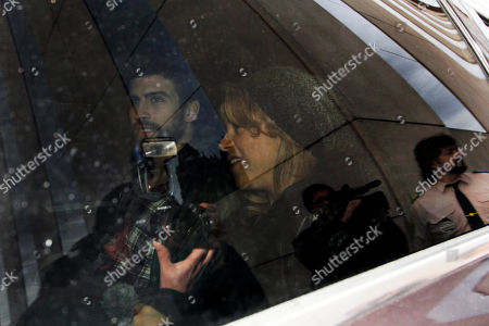 FC Barcelona's Gerard Pique, left, and Shakira, right, and their son, unseen, leave a hospital surrounded by media, in Barcelona, Spain, . Shakira, 35, gave birth to her first son, Milan Pique Mebarak on Tuesday, in Barcelona