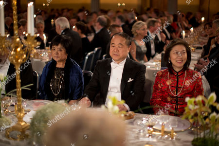 The 2012 Nobel Prize Laureate for Literature China's Mo Yan, center, sits beside his wife Du Qinlan left, during the 2012 Nobel Prize Banquet at the Town Hall in Stockholm