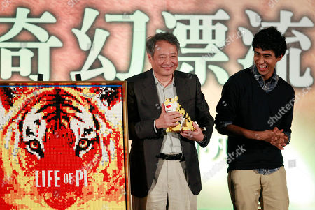 """Stock Photo of Suraj Sharma, Ang Lee Taiwanese director Ang Lee, left, and lead actor from India Suraj Sharma accept gifts a during press conference announcing their new film """"Life of Pi,"""" in Taipei, Taiwan, . """"Life of Pi"""" is an upcoming 3D adventure film based on the 2001 novel of the same name by Yann Martel, staring Sharma and directed by Lee"""