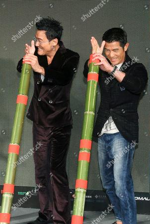 "Aaron Kwok, Tony Leung Ka Fai On, Hong Kong actors Aaron Kwok, right, and Tony Leung Ka Fai pose with bamboo poles during a promotional event for their new film ""Cold War"" in Taipei, Taiwan"