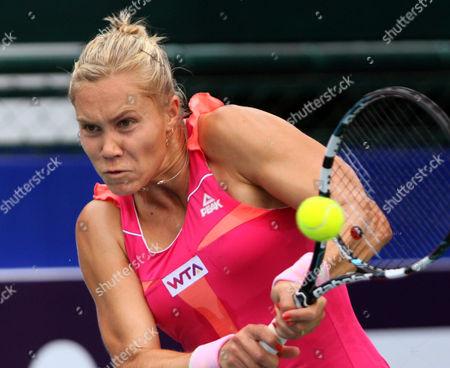 Nina Bratchikova of Russia returns a shot against Sabine Lisicki of Germany during their semifinal tennis match at the Pattaya Open tennis in Pattaya, Thailand