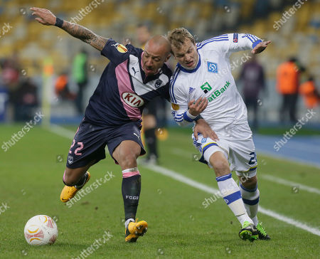 Julien Faubert of Bordeaux, left, and Oleh Gusev of FC Dynamo Kiev challenges for the ball during the Europa League round of 32 soccer match at the Olympiyskiy national stadium in Kiev, Ukraine