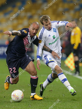 Julien Faubert of Bordeaux, left, and Oleh Gusev of FC Dynamo Kyiv challenges for the ball during the Europa League round of 32 soccer match at the Olympiyskiy national stadium in Kiev, Ukraine