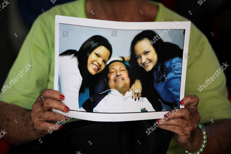 "A woman holds a newly purchased copy of a photo released by the government, showing Venezuela's President Hugo Chavez at the hospital in Havana, with two of his daughters, in Caracas,Venezuela. Venezuela's government said that President Hugo Chavez's respiratory problems have gotten worse and that the ailing leader is in ""very delicate"" condition. Communications Minister Ernesto Villegas said late in a statement read on national television that Chavez has a ""severe infection."" The 58-year-old Chavez first revealed an unspecified cancer in the pelvic region in June 2011, and reported undergoing radiation treatment and chemotherapy after earlier operations. He underwent cancer surgery in Cuba on Dec. 11 and flew back to Caracas on Feb. 18"