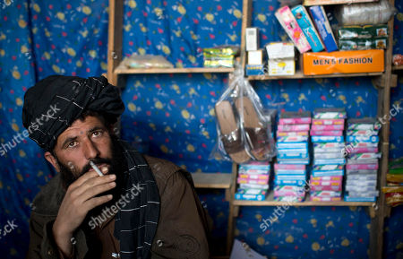 Shop owner Mohammed Haider enjoys a cigarette while waiting for customers at a local bazaar in Marjah, Helmand province, Afghanistan. Haider explains that poppy farmers who planted substitute crops are losing money because they can't sell their harvests. He predicts poppy production would double when foreign soldiers leave in 2014. In southern Helmand province, one of Afghanistan's deadliest battlefields, angry residents say 11 years of war has brought them widespread insecurity. Development that was promised hasn't materialized and the Taliban's rule is often said to be preferred