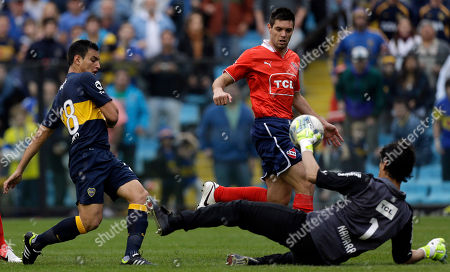 Independiente's goalkeeper Hilario Navarro, right, blocks a shot by Boca Juniors' Juan Sanchez Mino, left, as Independiente's Leonel Galeano eyes the ball during an Argentina's league soccer match in Buenos Aires, Argentina