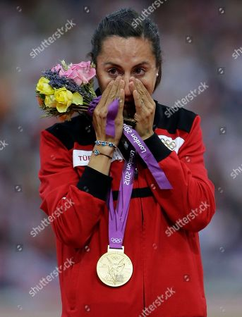 Turkey's Asli Cakir Alptekin poses with her gold medal for the women's 1500-meter during the athletics in the Olympic Stadium at the 2012 Summer Olympics, London. Olympic 1,500 meters champion Asli Cakir Alptekin of Turkey has agreed to give up her title and serve an 8-year ban for blood doping. The Court of Arbitration for Sport said it approved a settlement agreed by Alptekin and the IAAF
