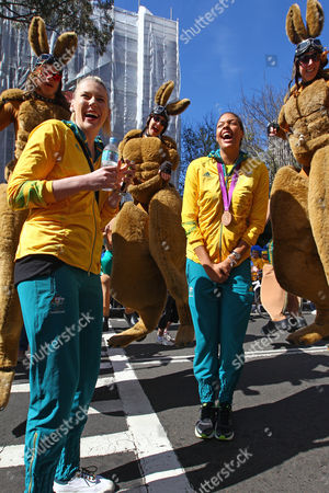 Australian women's basketball players Lauren Jackson, left, and Liz Cambage, with bronze medal, are surrounded by bouncing kangaroo characters during a welcome home parade for Australian Olympic Athletes in Sydney