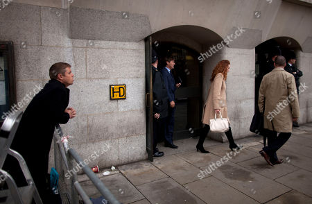 British actor John Alford, left, watches as Rebekah Brooks, center, the former chief of News Corp.'s British operations and her husband Charlie, third left, leave the Old Bailey court in the City of London, . Rebekah Brooks and Andy Coulson, the ex-communications chief for Prime Minister David Cameron, learned Wednesday that they will face trial next September over allegations linked to phone hacking