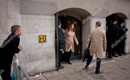 British actor John Alford, left, watches as Rebekah Brooks, center, the former chief of News Corp.'s British operations leaves after appearing in her phone hacking case at the Old Bailey court in the City of London, . Brooks and Coulson appeared in London's Old Bailey court Wednesday for a hearing along with five other people charged in connection with the phone hacking scandal that originated at the News of the World tabloid and rocked Rupert Murdoch's News Corp. empire. Rebekah Brooks, the former chief of News Corp.'s British newspapers, and Andy Coulson, the ex-communications chief for Prime Minister David Cameron, learned Wednesday that they will face trial next September over allegations linked to phone hacking
