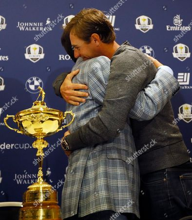 Europe's Ryder Cup Captain José María Olazabal, left, and player Nicolas Colsaerts, right, of Belgium hug after a press conference at Heathrow in London . Erasing some of their worst Ryder Cup memories, the Europeans wore the image of Seve Ballesteros on their sleeves and played their hearts out Sunday at Medinah to match the greatest comeback in history and head home with that precious gold trophy