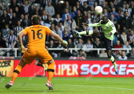 Newcastle United's Papiss Cisse, right, has a shot towards goal past Bordeaux's goalkeeper Cedric Carrasso, left, during their Europa League group D soccer match at the Sports Direct Arena, Newcastle, England