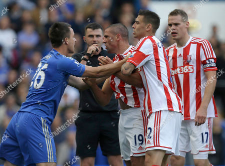 Chelsea's John Terry, left, holds back Stoke City's Jonathan Walters, No. 19, as he reacts to a foul by Chelsea's David Luiz, unseen, during their English Premier League soccer match at Chelsea Stamford Bridge stadium in London