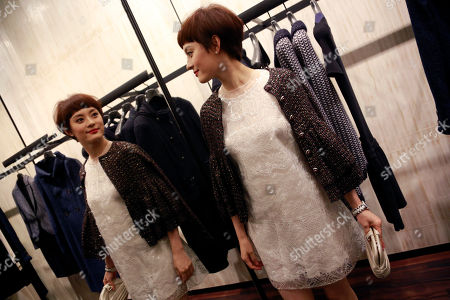 Sun Li Chinese actress Sun Li looks herself in the mirror at a Chanel shop as part of Vogue Fashion's Night Out event in Shanghai, China