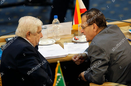Stock Photo of Walid al-Moallem, Ali Shami Syrian Foreign Minister Walid al-Moallem, left, listens to his Lebanese counterpart Adnan Mansour at the Nonaligned Movement summit in Tehran, Iran