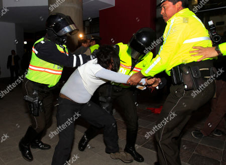 Police officers grab a demonstrator during clashes after a protest outside the United Kingdom's embassy in Quito, Ecuador, . Ecuador accused Britain on Wednesday of threatening to storm its London embassy to arrest Julian Assange after the U.K. issued a stern warning to the South American nation ahead of its decision on an asylum bid by the WikiLeaks founder. People protested against the alleged threat