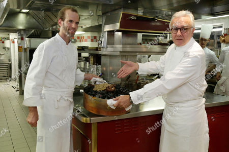 Dan Barber, Alain Ducasse This photo shows American Chef Dan Barber, left, and Alain Ducasse displaying a Cossabow Pig plate in the kitchen of the Plaza Athenee in Paris. He fires up the succulent pork over gnarled, carbonated pig bones, grows sweet greens in a soil mixed with pumice that's left over by the hazelnut oil industry and he's creating a new kind of wheat, named after himself _ Dan Barber