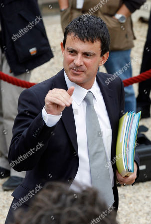 French interior minister Manuel Valls waves to newsmen as he leaves the Elysee Palace following the weekly cabinet meeting in Paris, . President Francois Hollande and Manuel Vals are taking up a proposal to tighten France's anti-terrorism laws and deter French youths from traveling abroad for training in paramilitary camps like those run by radical Islamists
